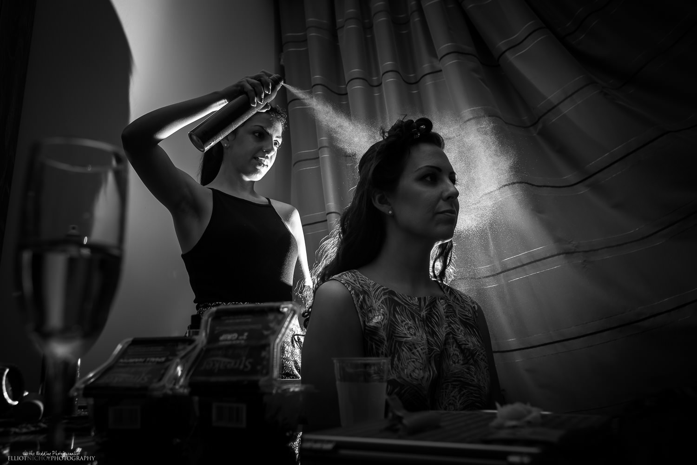 hair stylist applying hairspray to a bridesmaids hair in a Westin hotel room in Malta