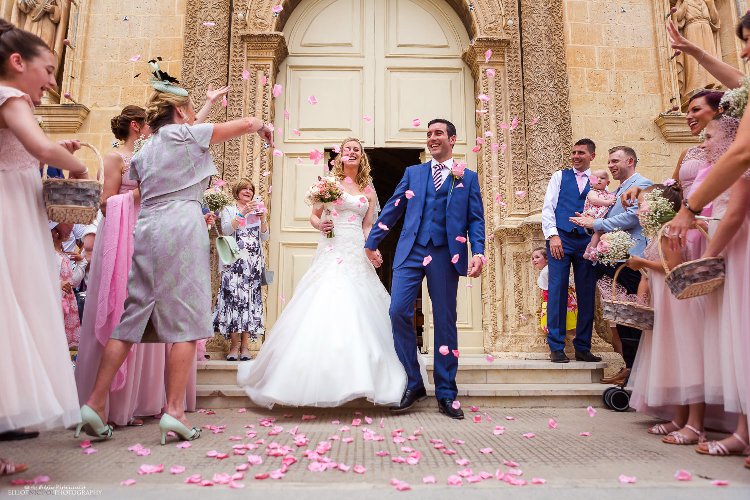 Bride & Groom showered in pink confetti outside St Mary's parish church in Attard, Maltaee