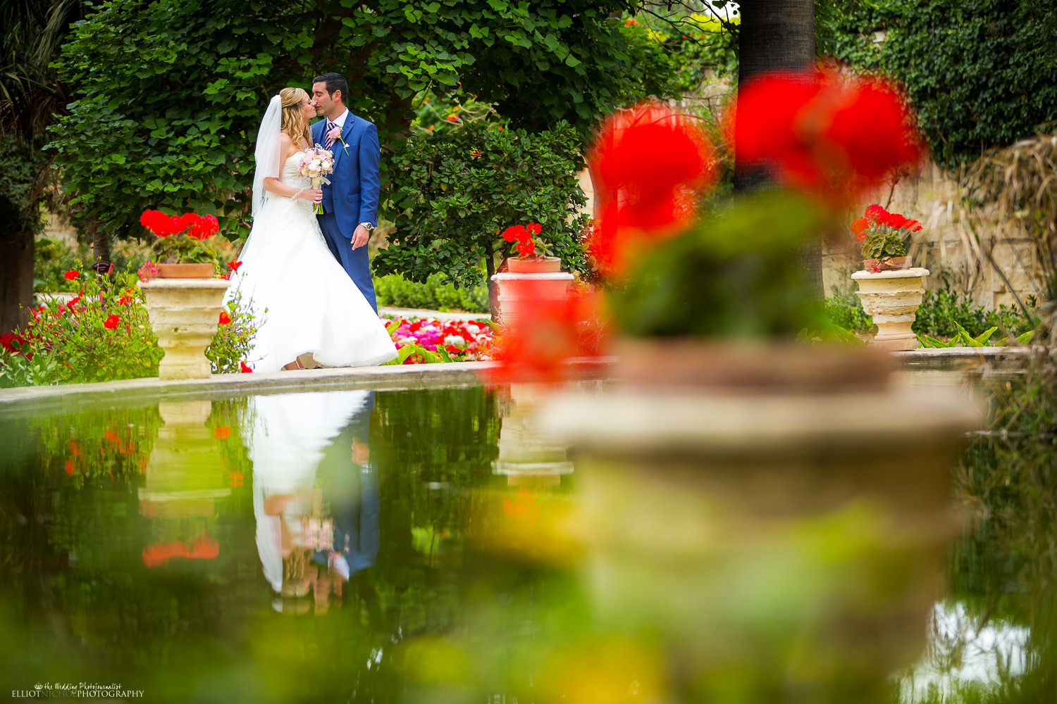 Newlyweds kissing in san Anton gardens in Attard reflection in a pond
