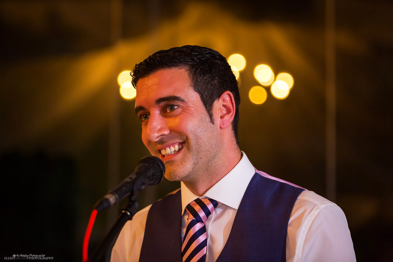 Groom smiling while performing his wedding speech