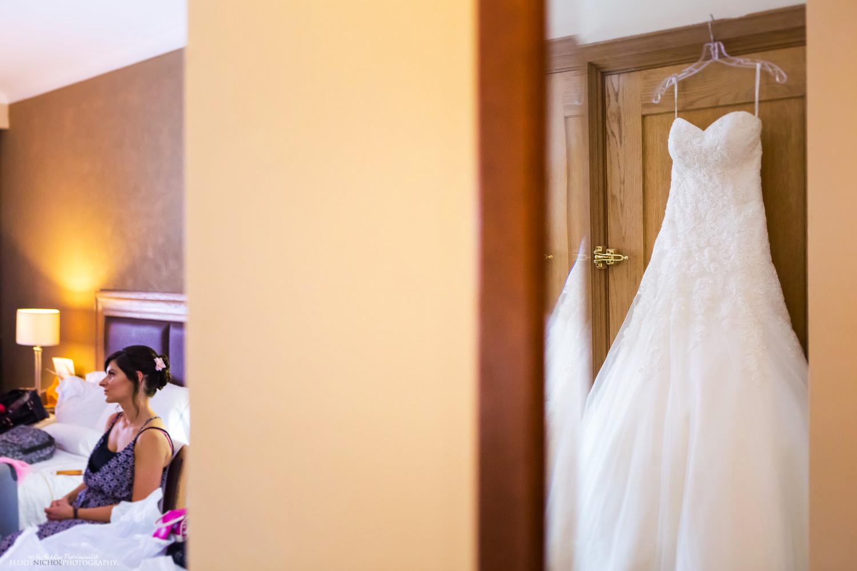 Wedding dress hanging on door reflected in a mirror