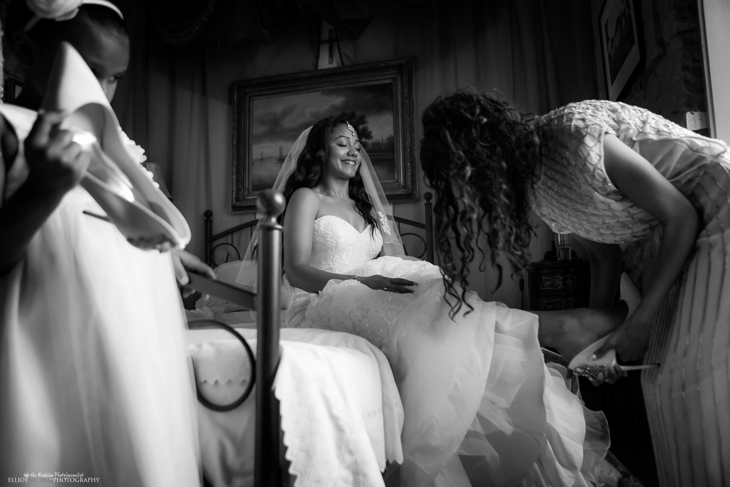 Bride putting on her wedding shoes with some help from her bridesmaid.