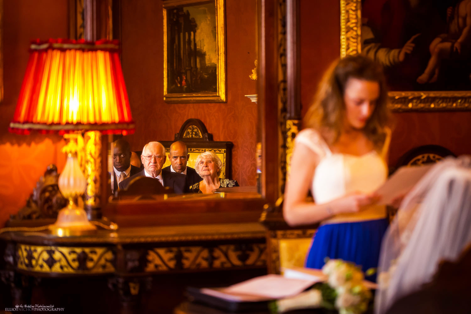 Wedding guests reflected in a wall mirror during the wedding ceremony in the Sala Lombarda room at the Palazzo Parisio in Malta.