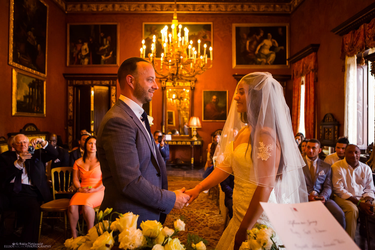 Bride and Groom hold hands during the wedding ceremony at the Palazzo Parisio.