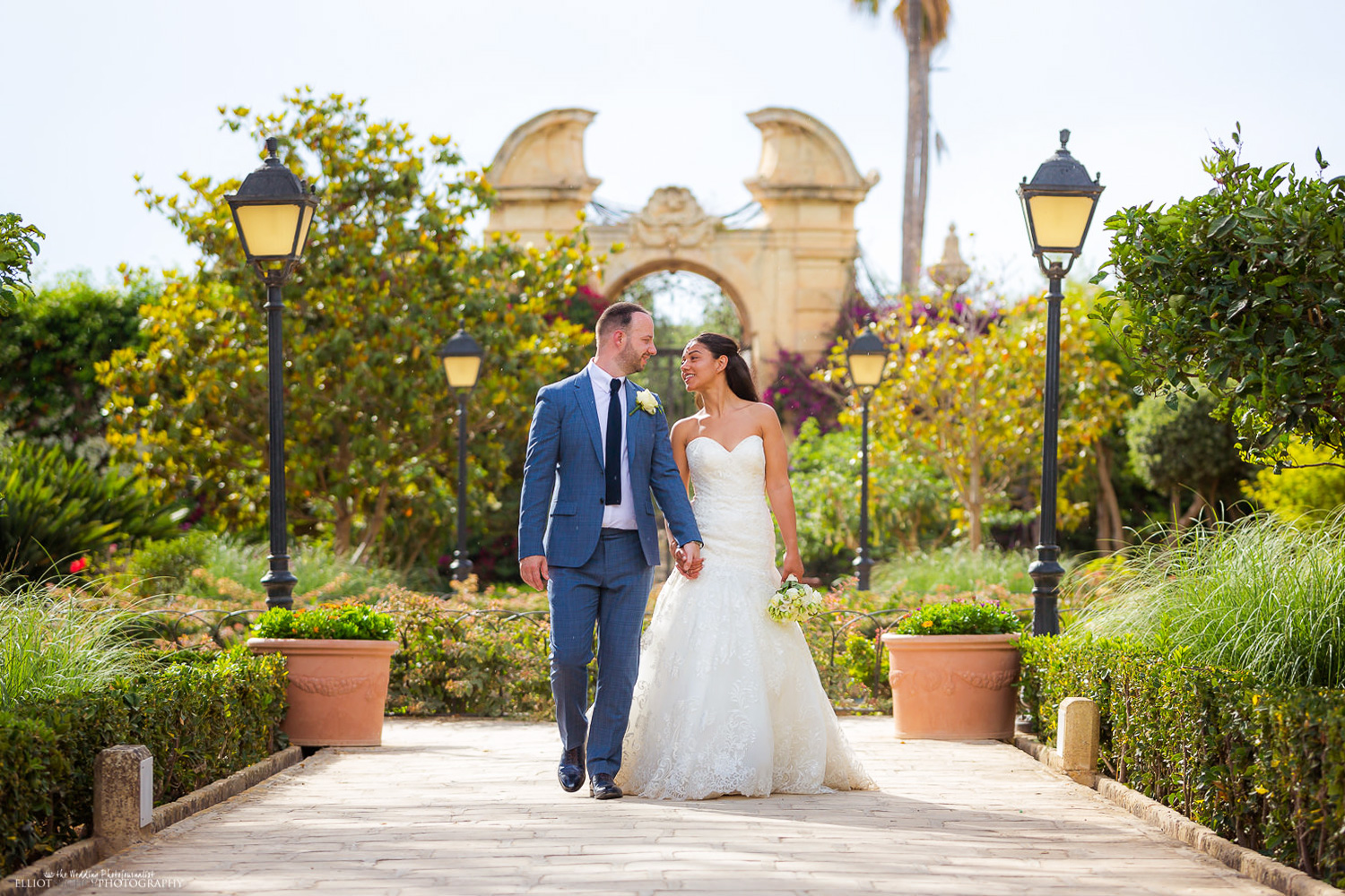 Bride and Groom walk in the Palazzo Parisio Gardens.