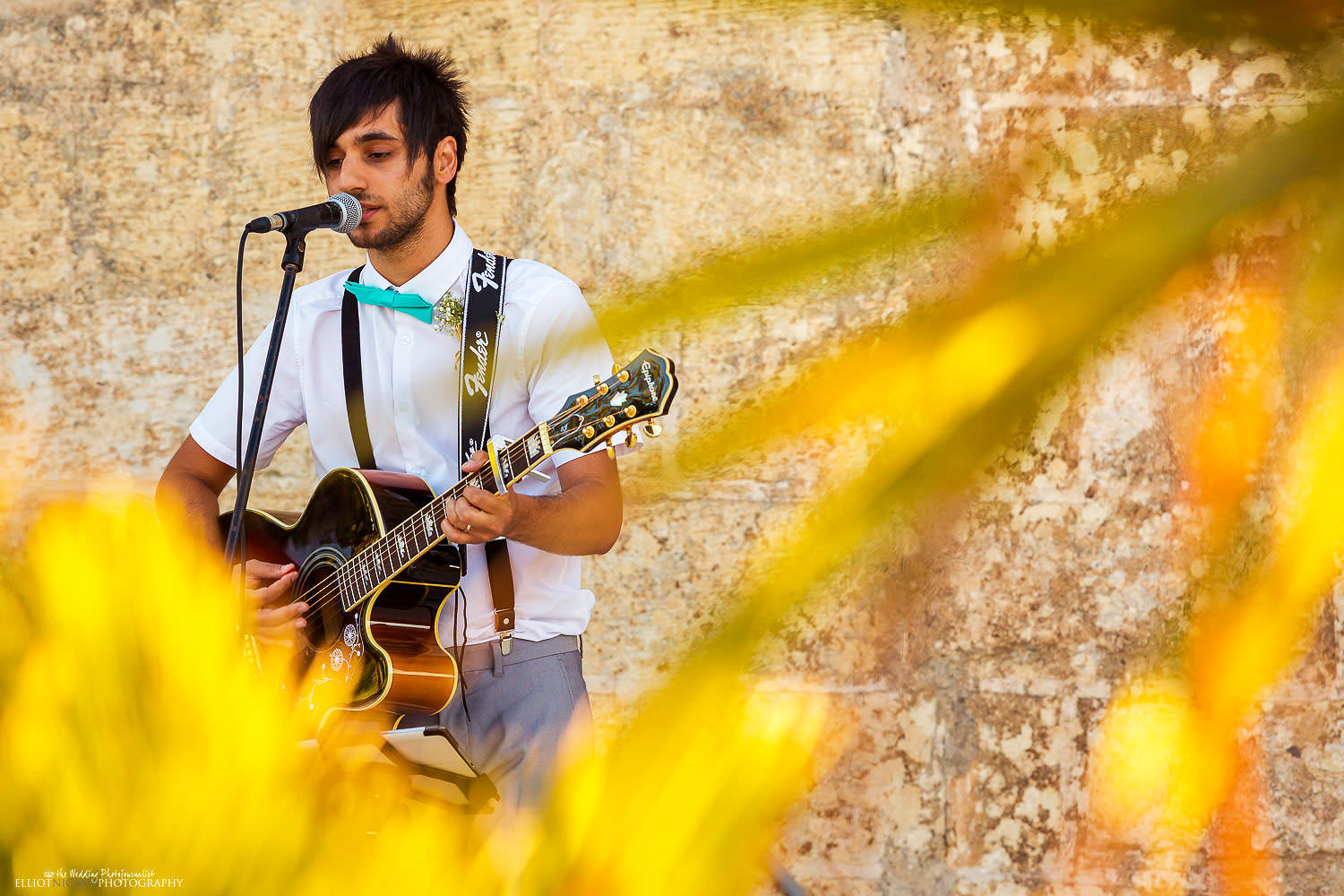 Wedding guest plays his guitar during the wedding ceremony