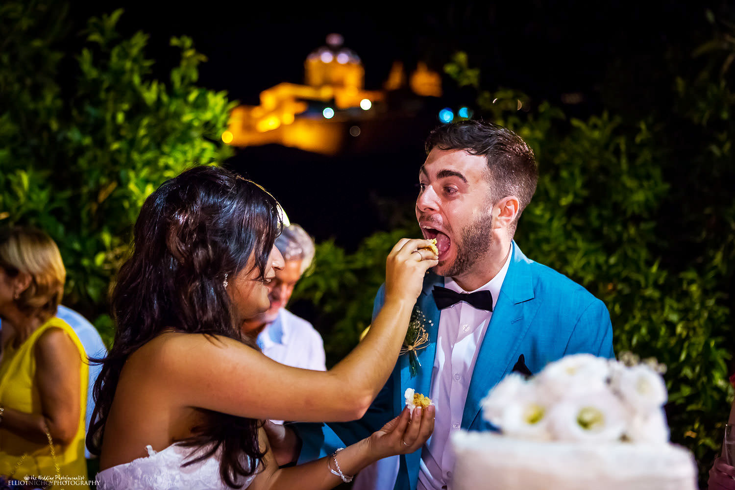 Bride feeding wedding cake with her groom with Mdina in the background, Malta