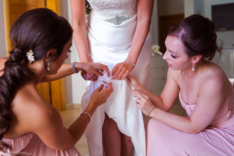 bridesmaid put brooch pin inside brides wedding dress.