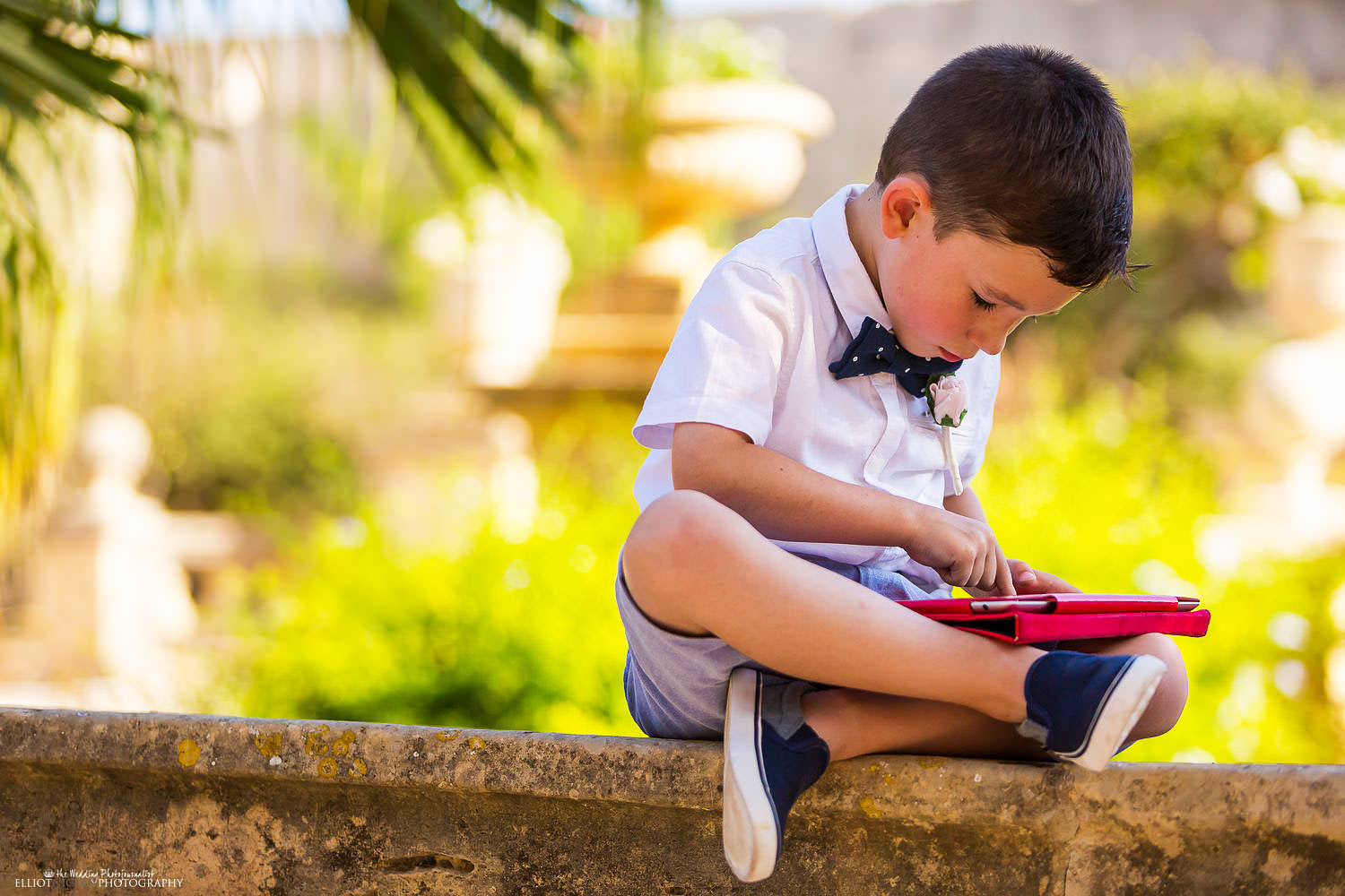 young wedding guest plays on his tablet.