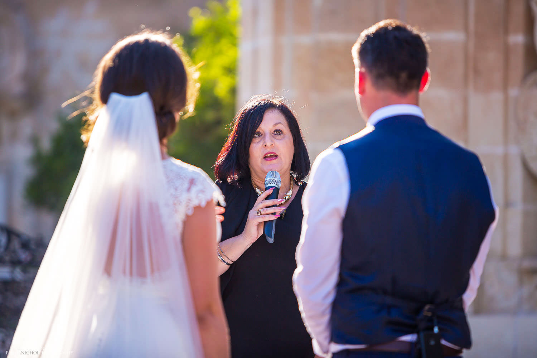 bride and groom with registrar in the Baroque gardens at Villa Bologna, Malta.