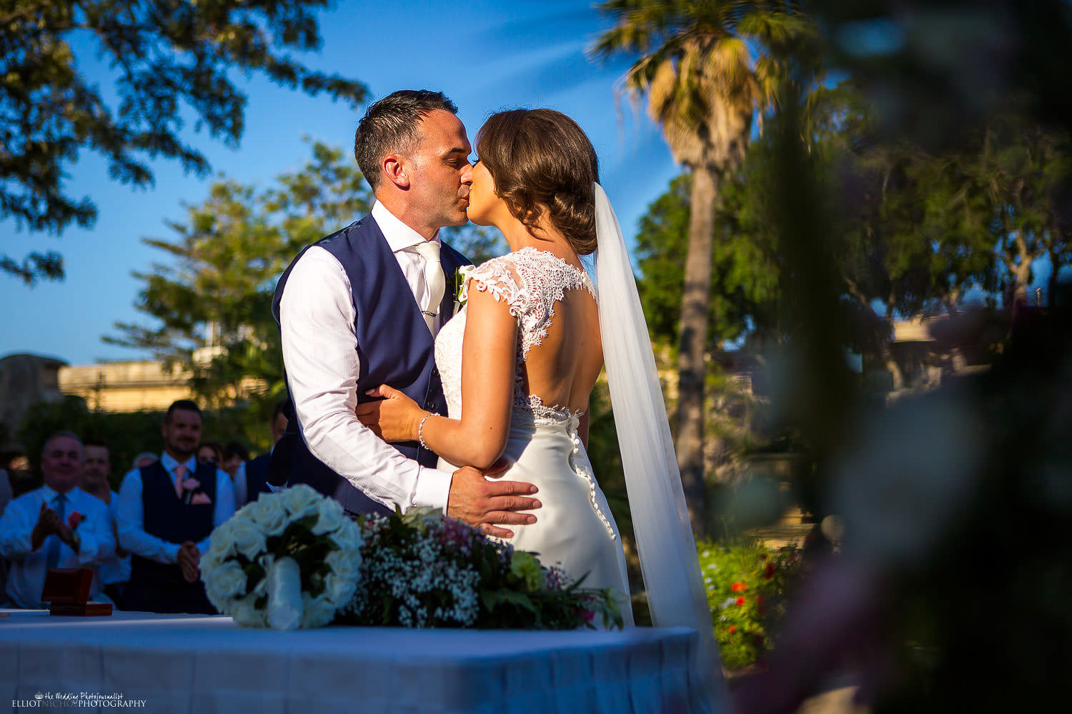 hasband and wife kiss for the frist time in the gardens of Villa Bologna, Malta.