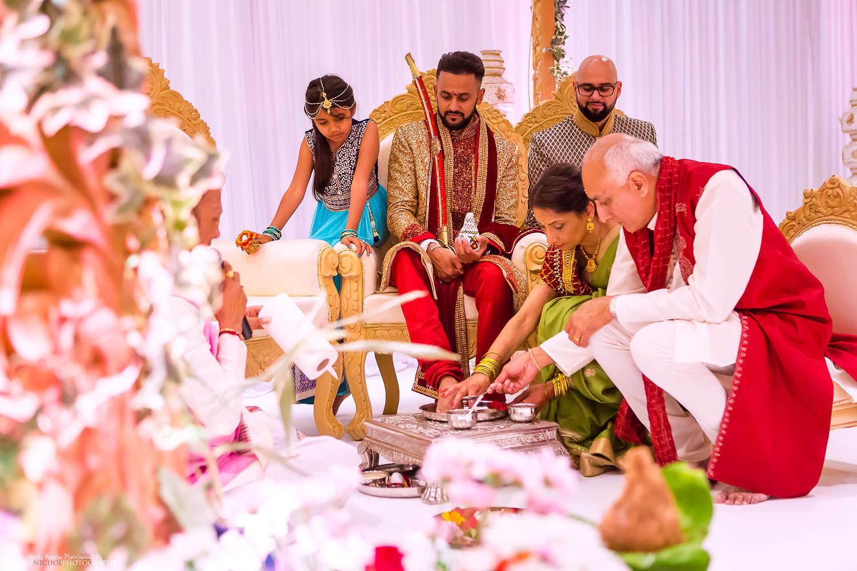 IndianBride's family surround the groom during the Hindu wedding ceremony. Photo by Newcastle Upon Tyne based wedding photojournalist Elliot Nichol.