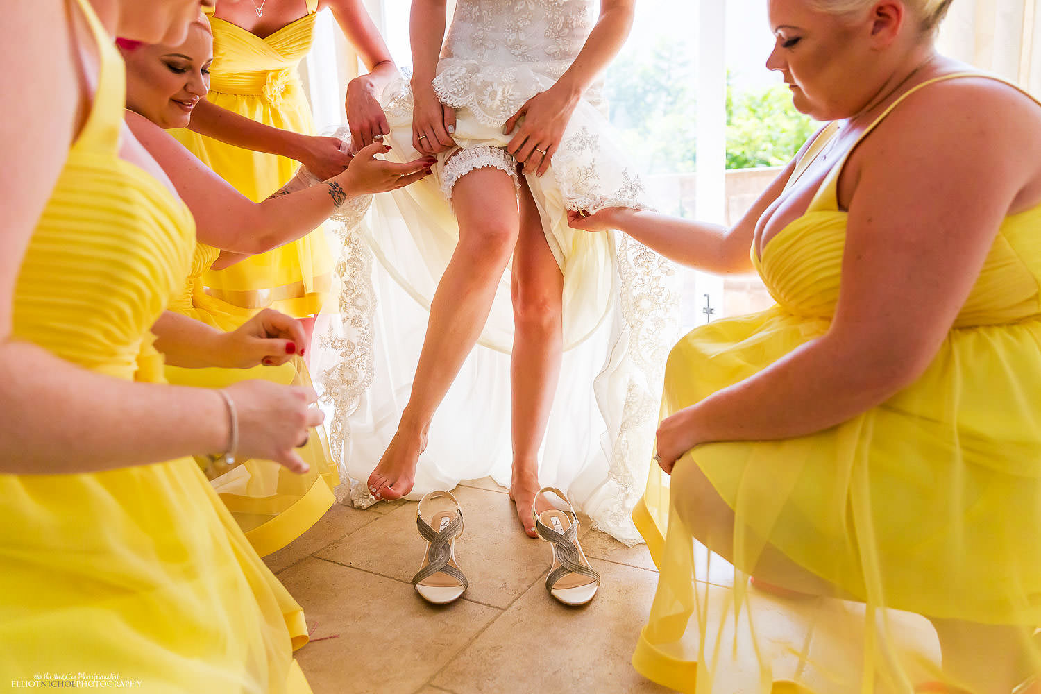 Bride being helped into her wedding dress by her bridesmaids.