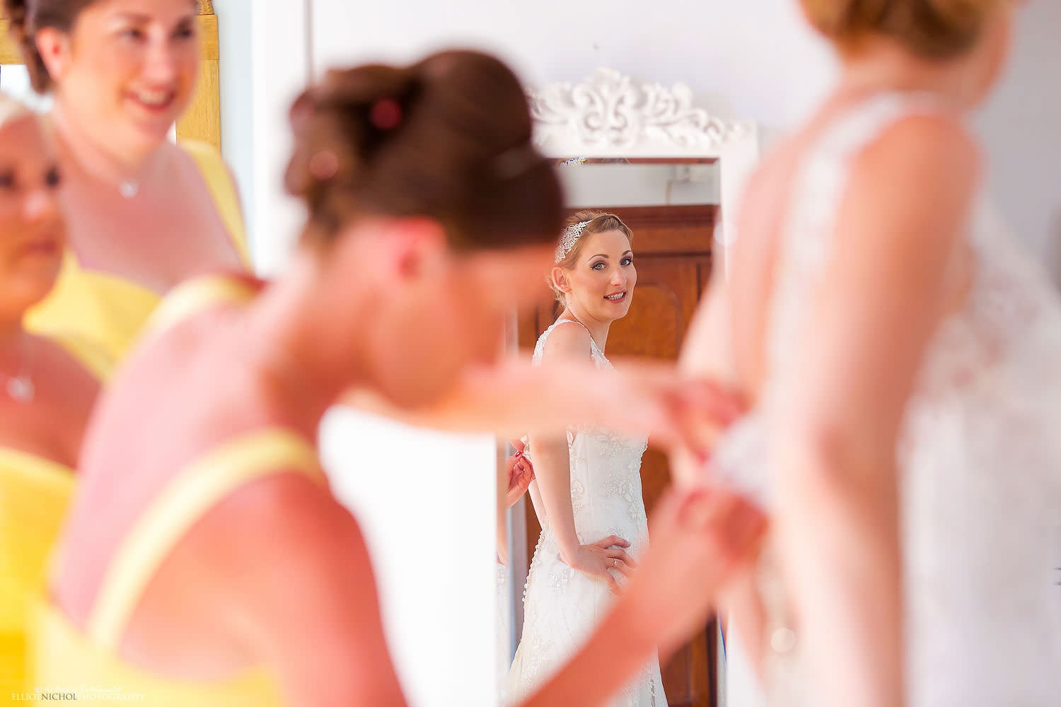 Destination bride getting into her dress of the morning of her wedding day with her bridesmaids.