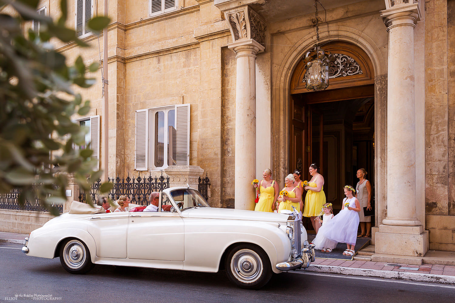 Bride and her father arrive in vintage wedding car at the Palazzo Parisio in Naxxar, Malta.