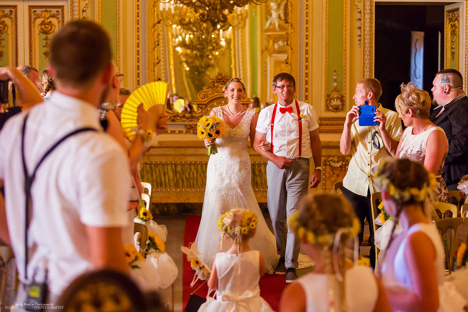 Bride and her father walk down the aisle in the golden Ballroom of the Palazzo Parisio to the wedding ceremony.