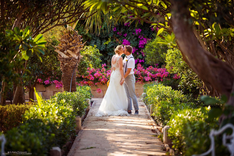 Destination wedding - couple kissing in the gardens of the Palazzo Parisio in Malta.