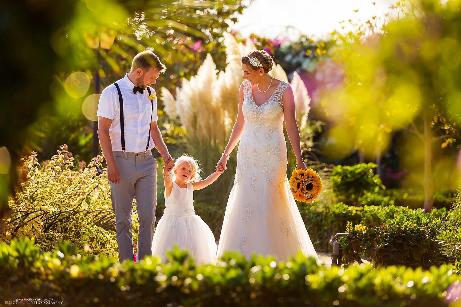 Palazzo Parisio weddings - destination wedding photographer capturing newlyweds with their young daughter in the gardens of the Palazzo Parisio in Naxxar, Malta.