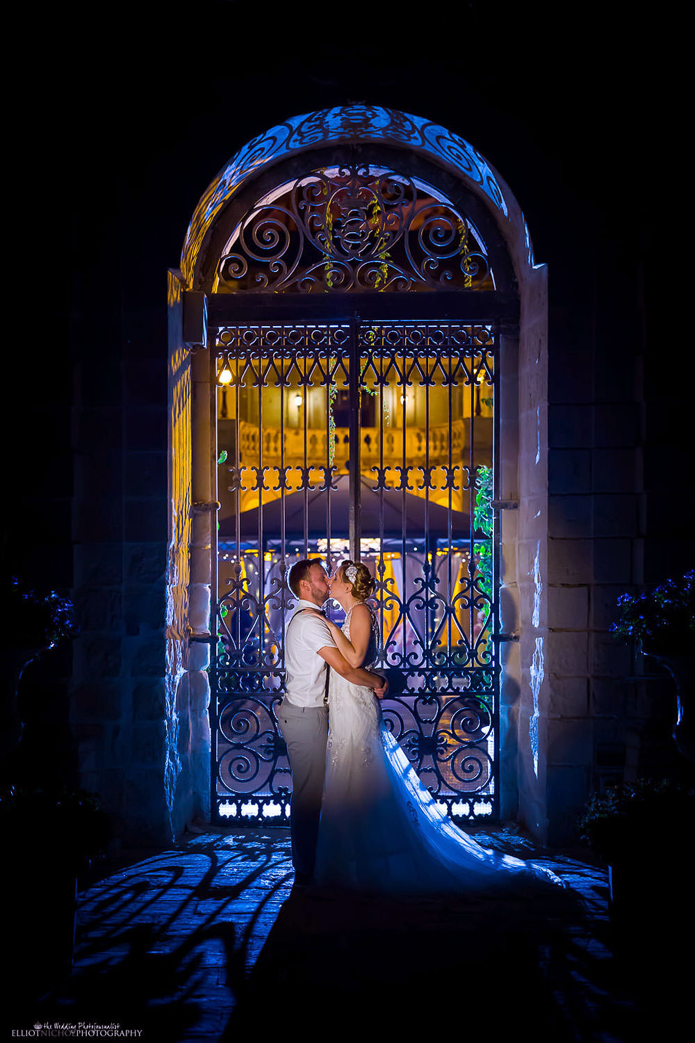 Bride and groom kiss at the Palazzo Parisio garden gates during their destination wedding in Malta.
