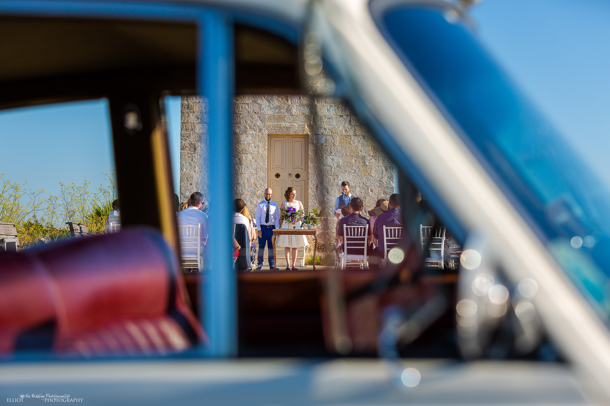 View through the vintage wedding car's window of the wedding blessing ceremony. Newcastle Upon Tyne based wedding photographer Elliot Nichol photographing destination weddings.