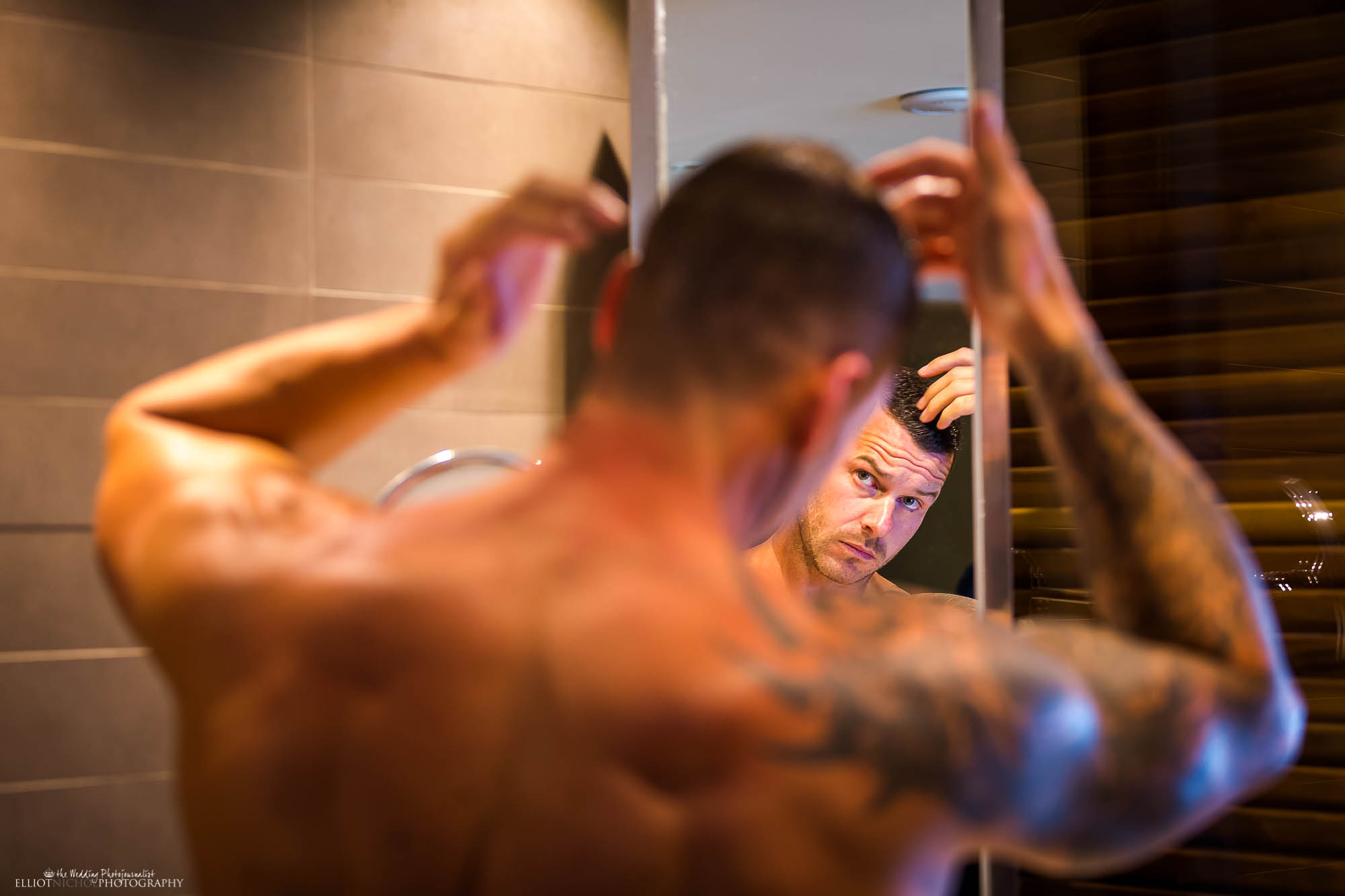 Groom in front of the mirror getting ready for his wedding. Newcastle Upon Tyne based wedding photography.