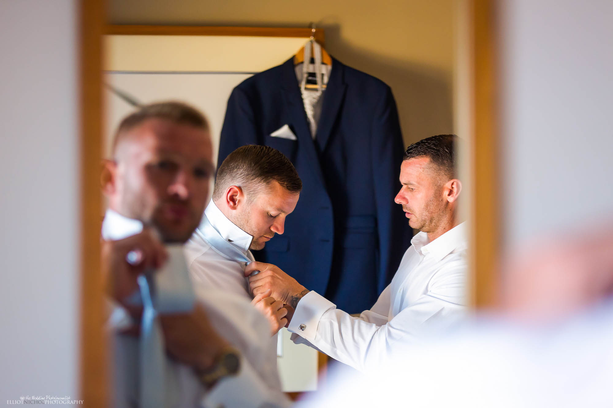 Navy blue wedding suit hanging up behind the groom helping his groomsmen get ready for the wedding.