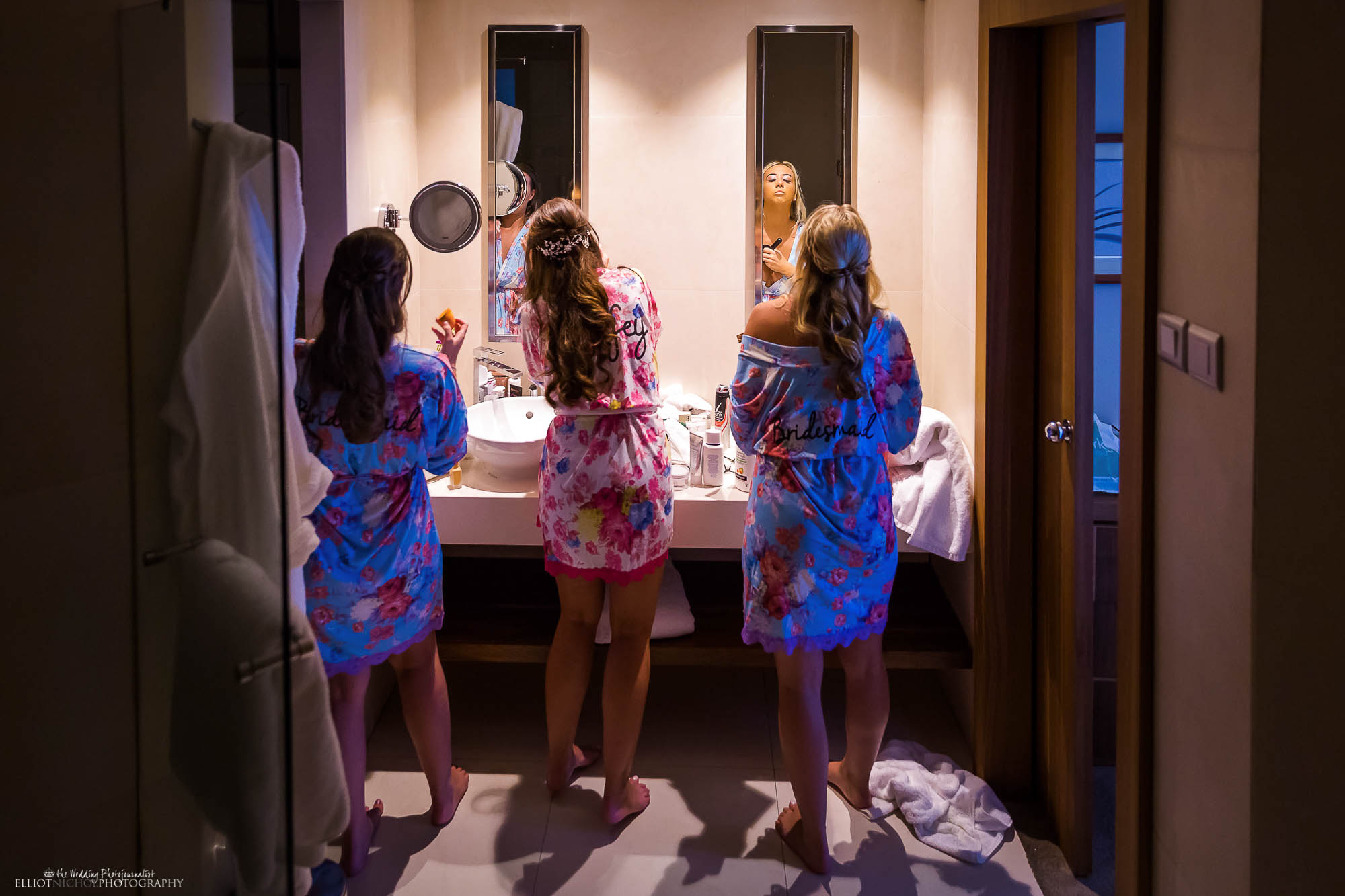 Bride with her two bridesmaids getting ready in the bathroom. Wedding photographer Elliot Nichol.