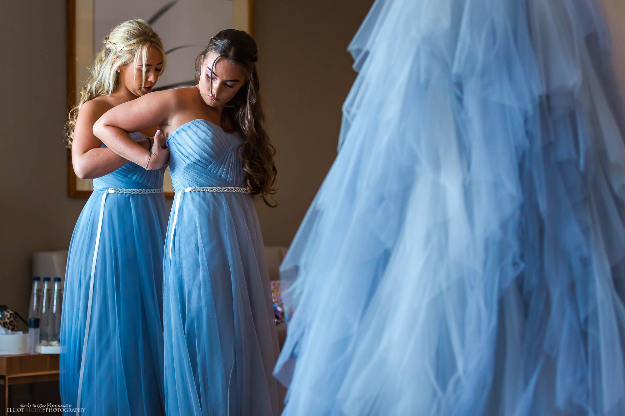 Bridesmaids helping each other into their blue bridesmaid dresses. North East wedding photography