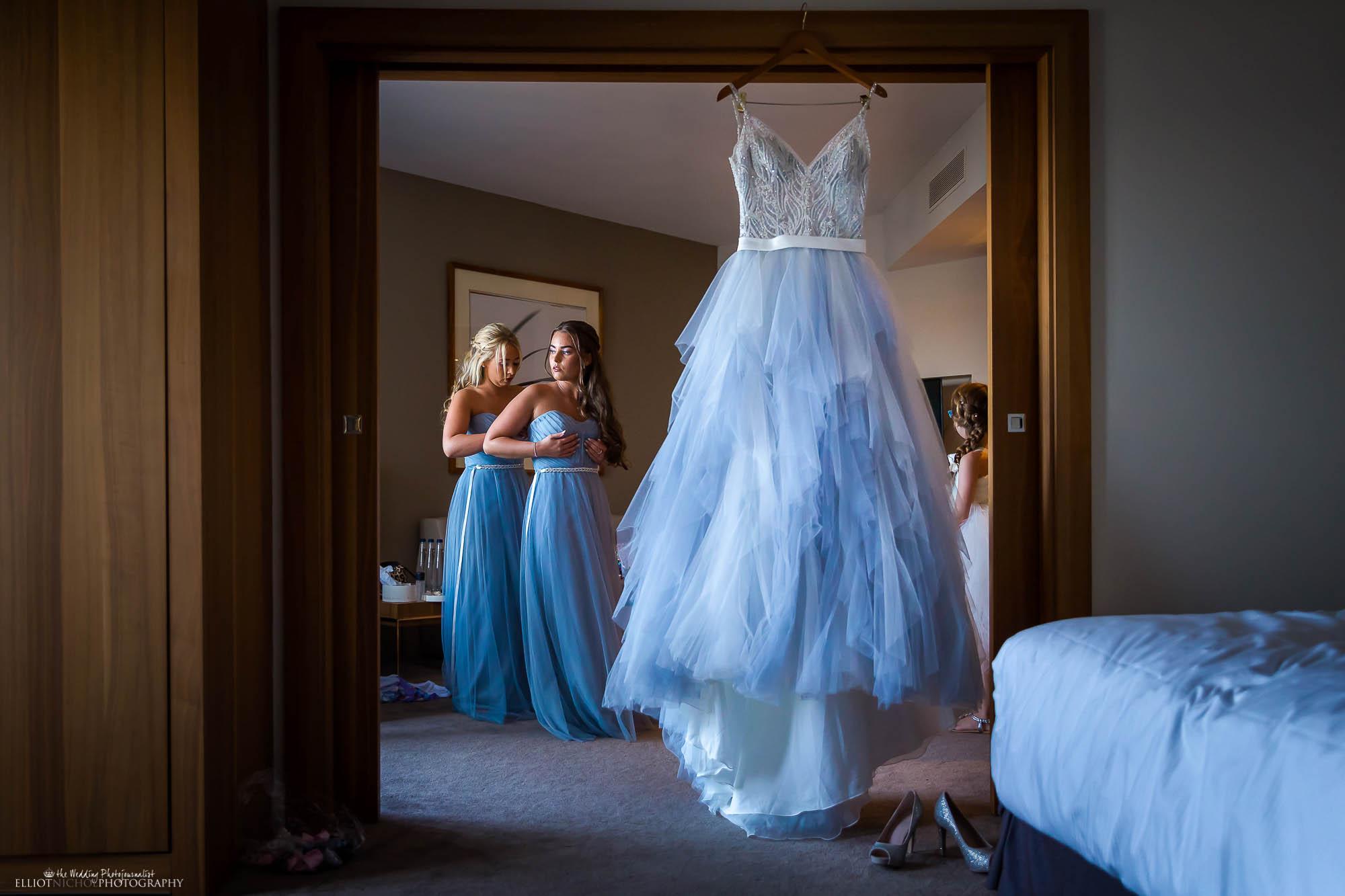 Bridesmaids getting ready next to brides blue wedding dress hanging in the room. Wedding photographer Elliot Nichol.
