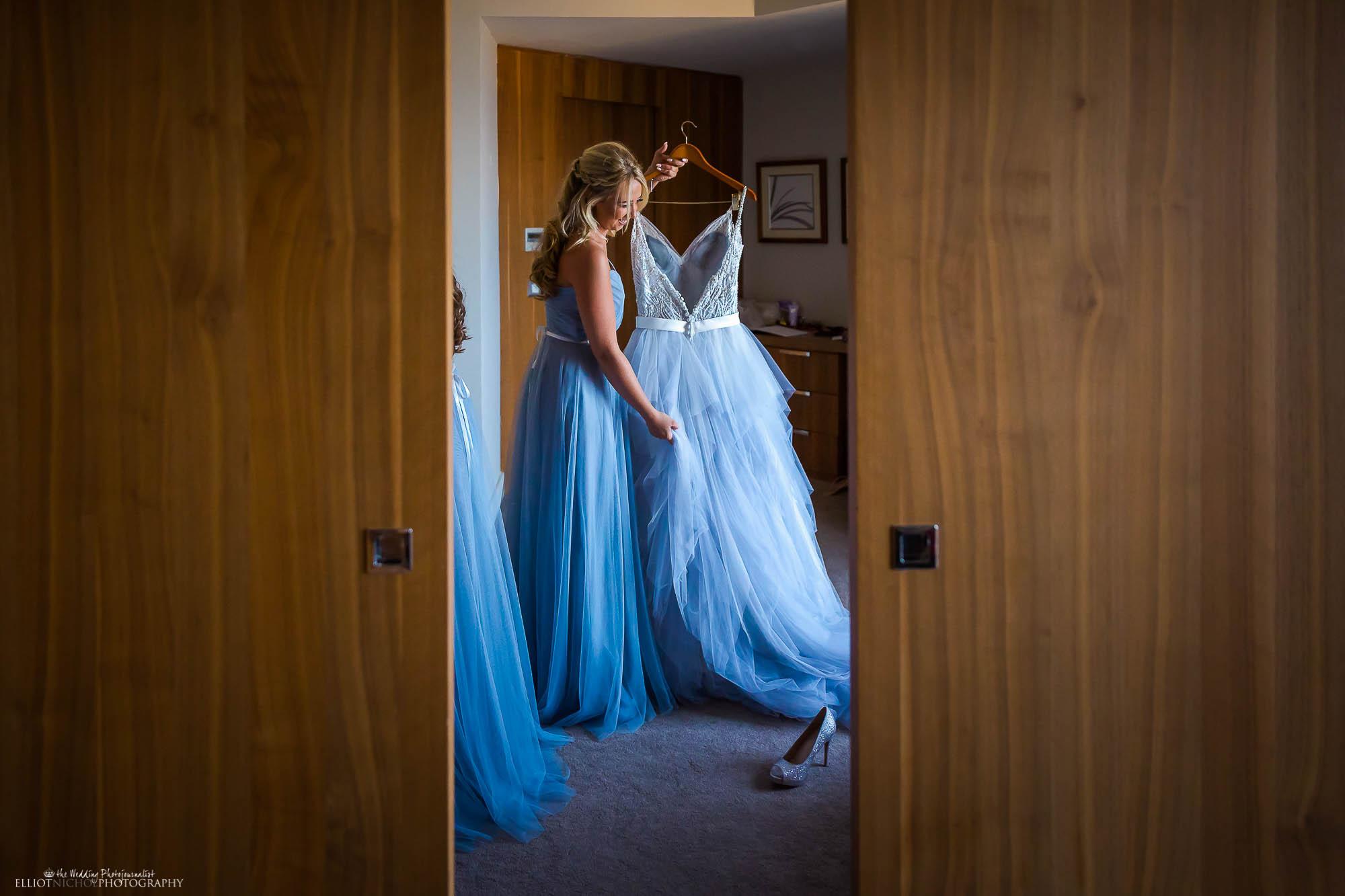 Bridesmaid holding brides blue wedding dress. Newcastle Upon Tyne based wedding photographer Elliot Nichol.