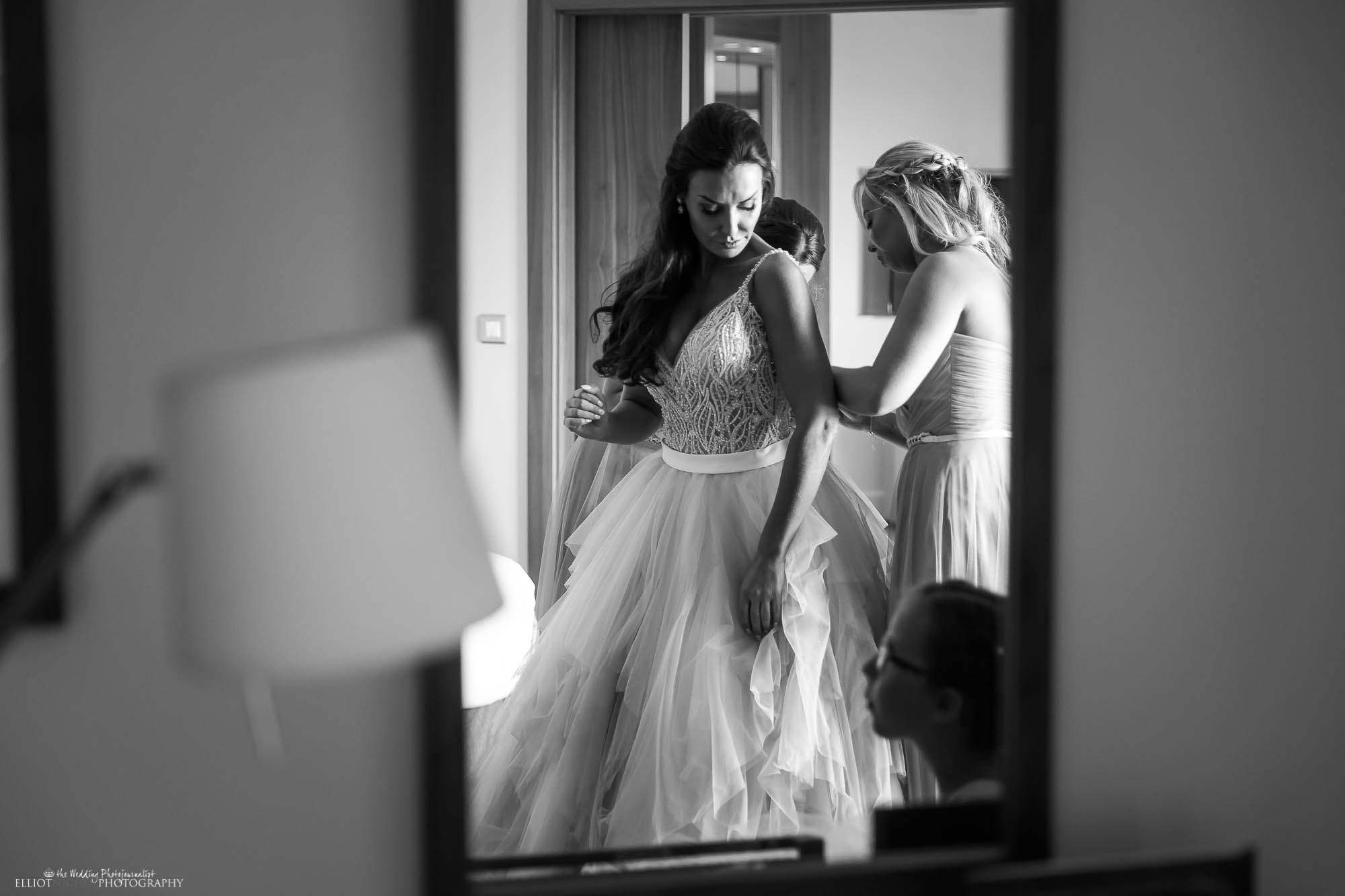 Bride gets into her wedding dress with the help of her bridesmaids.