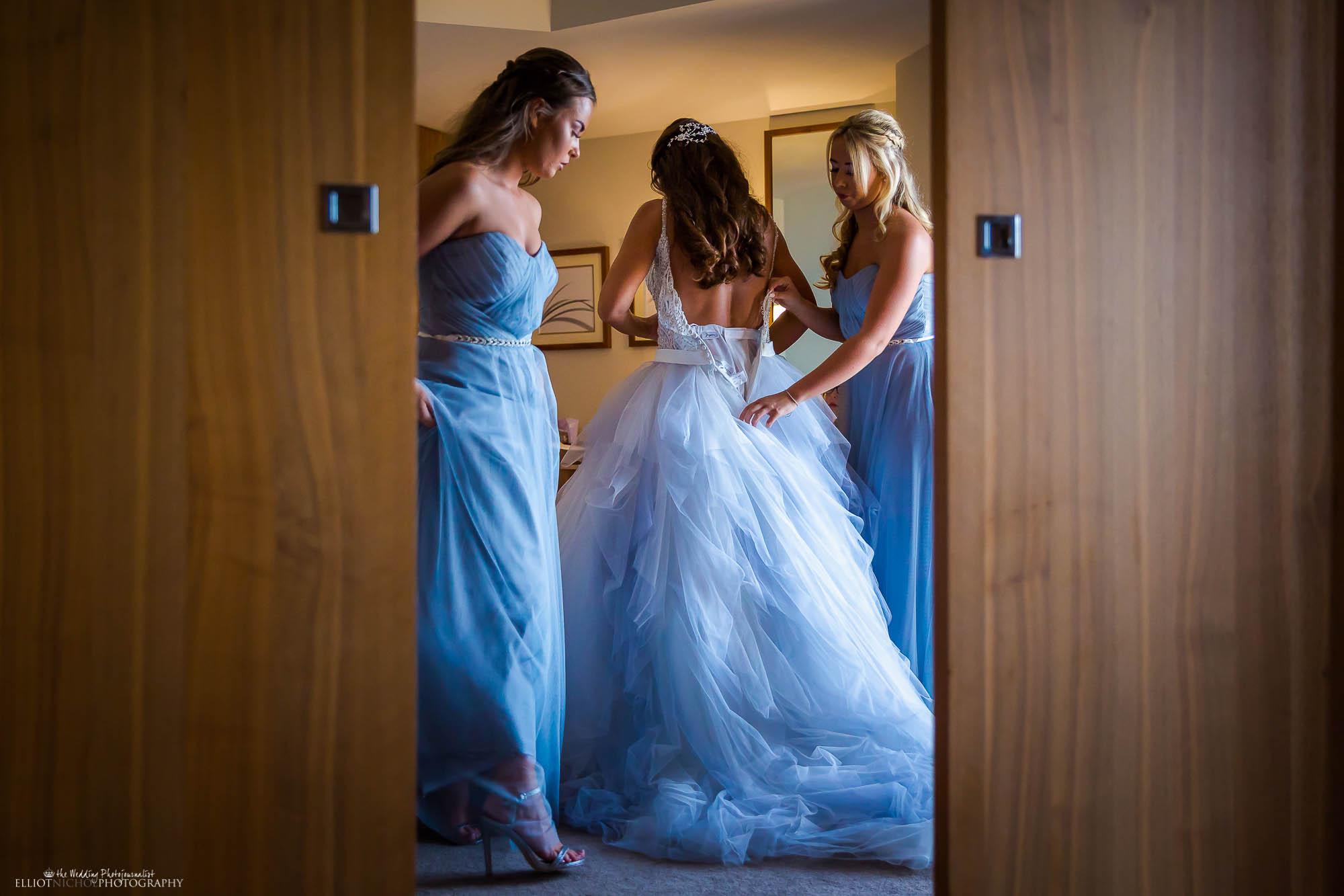 Bride helped into her wedding dress by her bridesmaids. Northeast wedding photographer.