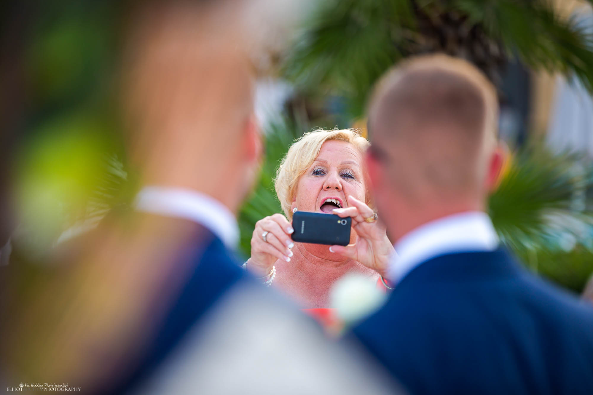 Wedding guests takes a photo of the groom and his Bestman before the wedding ceremony starts.