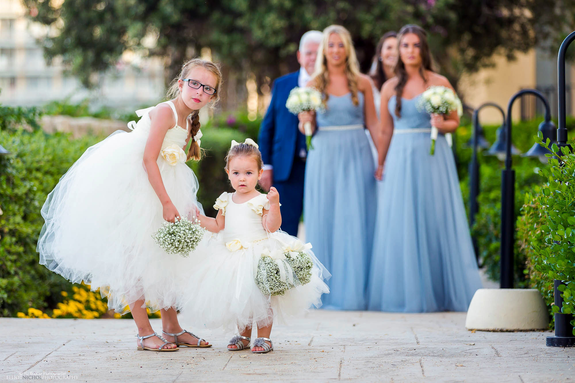 Flower girls followed by bridal party at the start of the wedding procession to the ceremony.