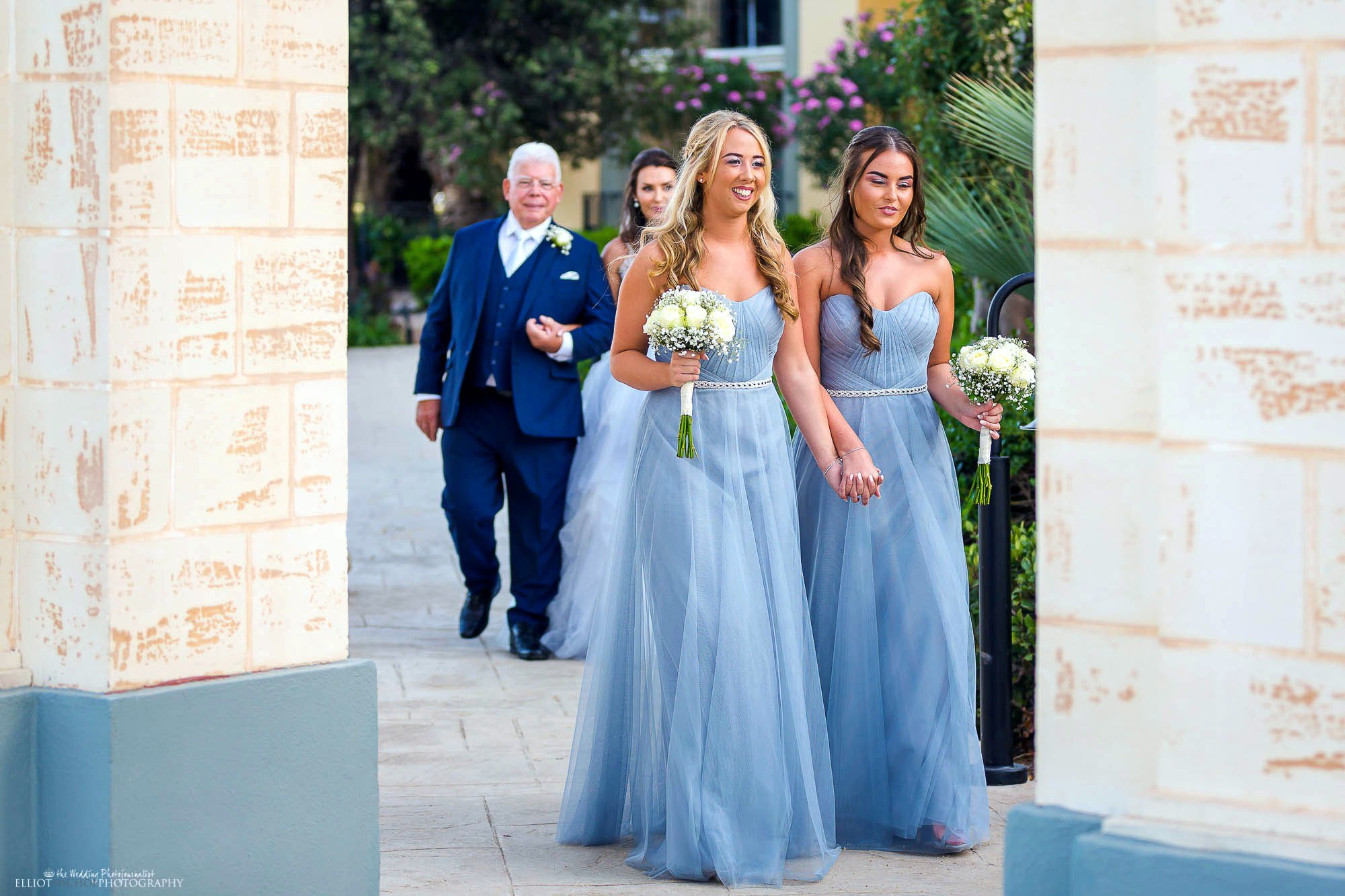 Bridesmaids in their blue dresses walk together during the procession towards the wedding ceremony. North East wedding photographer.