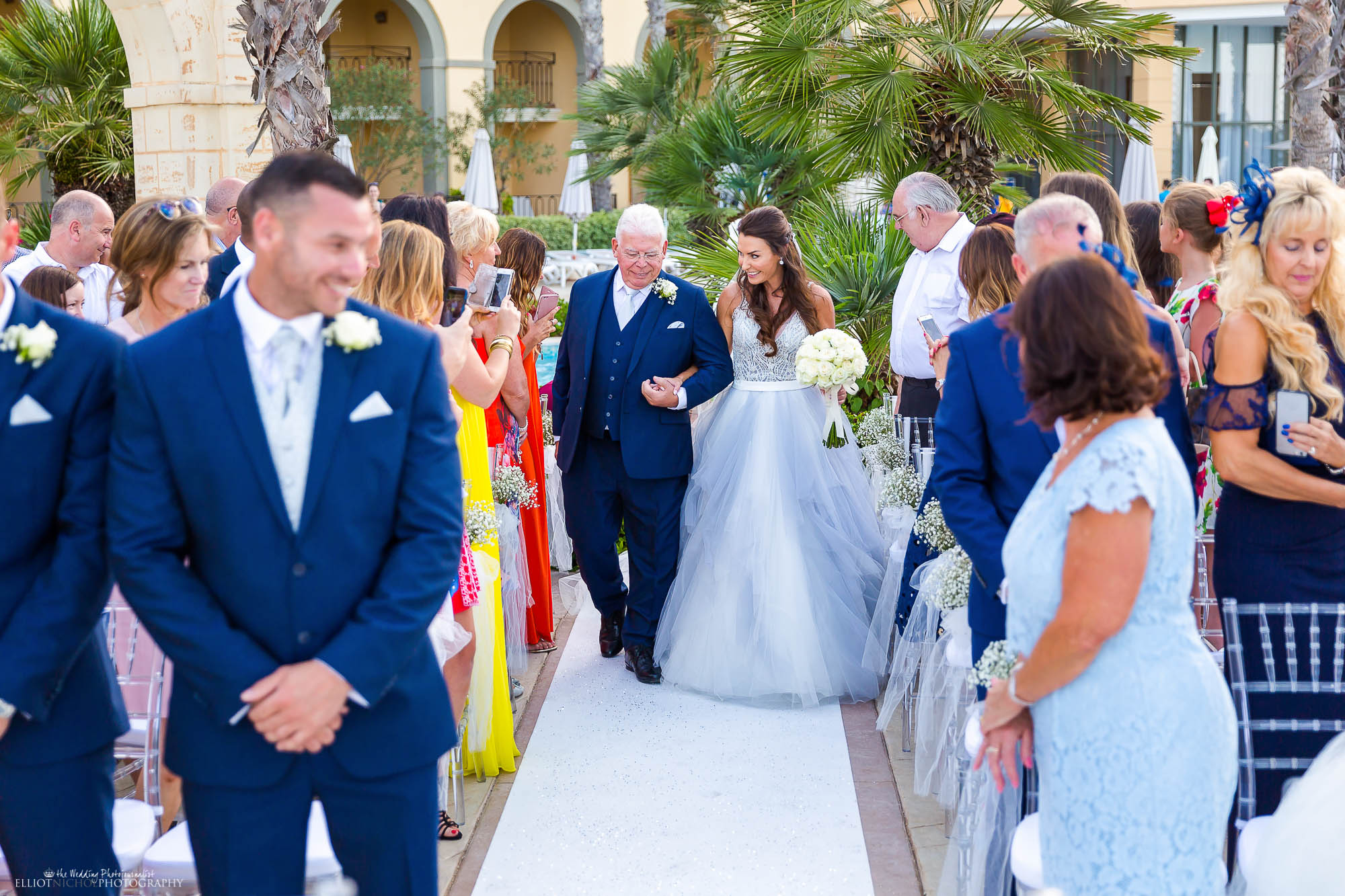 Bride arrives at her wedding ceremony with her father in her blue wedding dress.