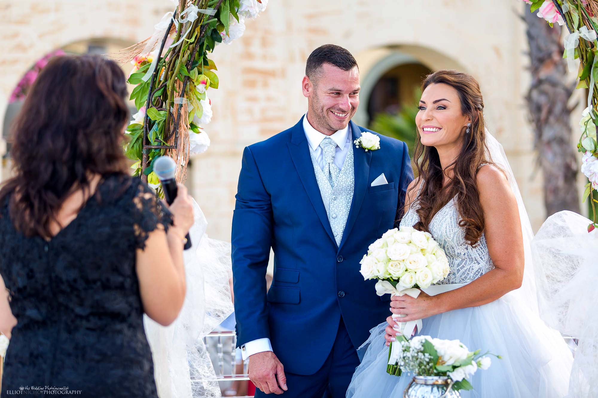 Bride and groom in their blue wedding suit and dress. Wedding photography by Elliot Nichol.