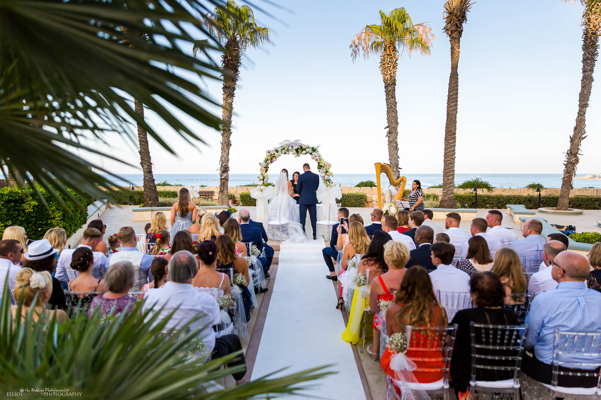 Perfect destination wedding under the palm trees and over looking the blue sea. Blue wedding dress wedding.
