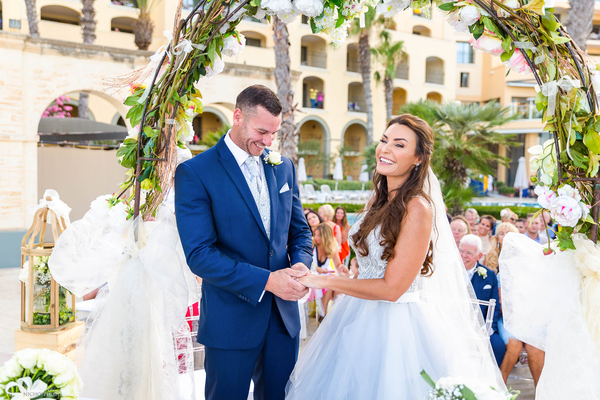 Groom exchanges the rings with his bride in her blue wedding dress.