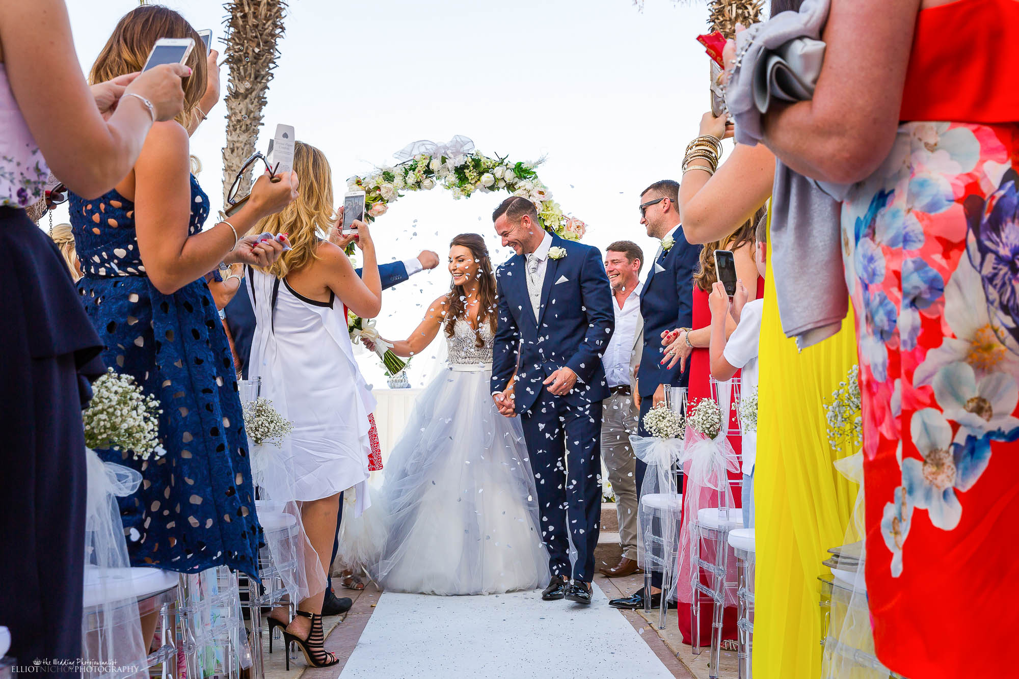 Bride in her blue wedding dress walks down the aisle with the groom under a shower of confetti. Wedding photography by North East photographer Elliot Nichol