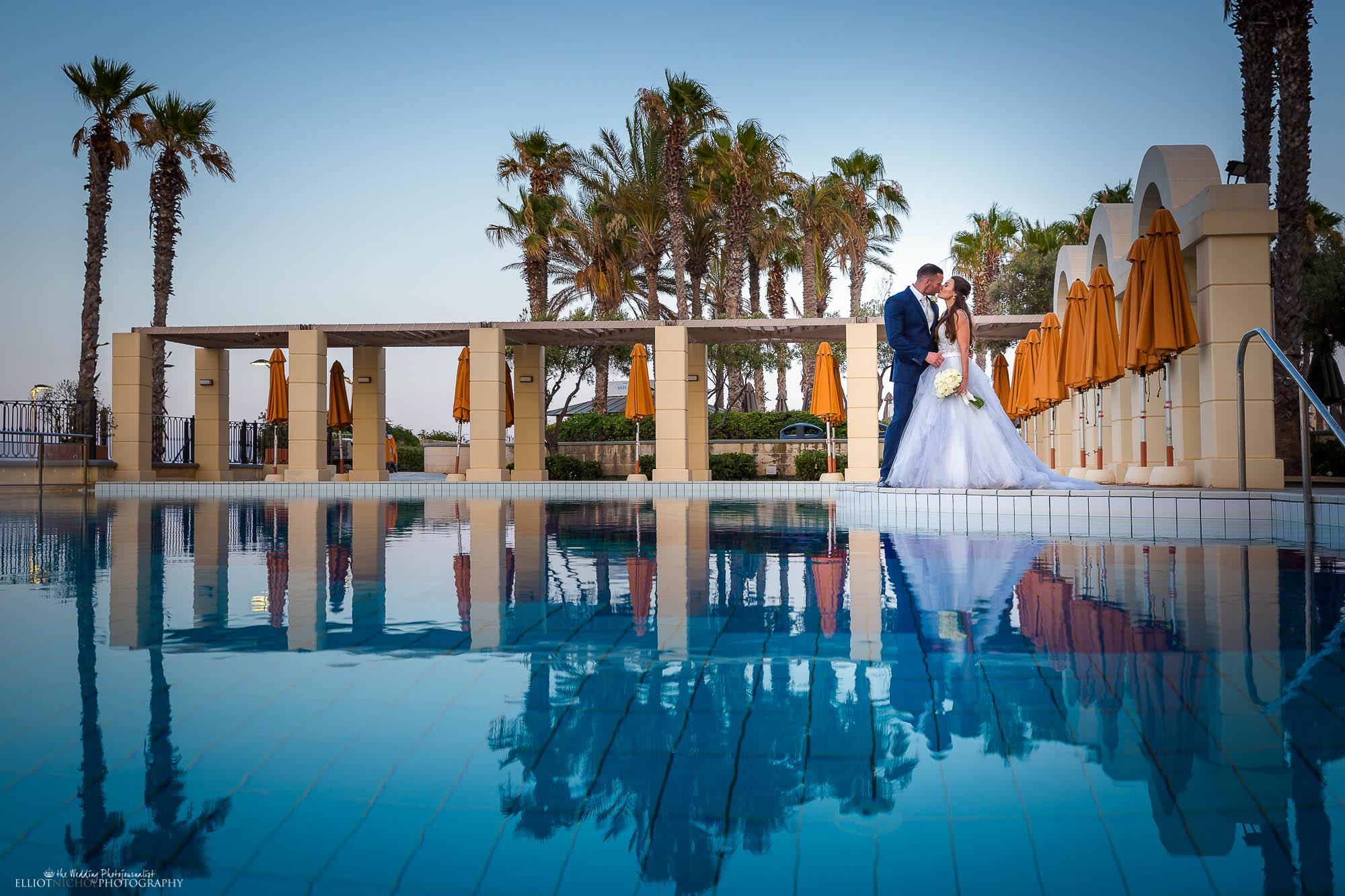 Destination newlyweds kissing by their wedding venue swimming pool.