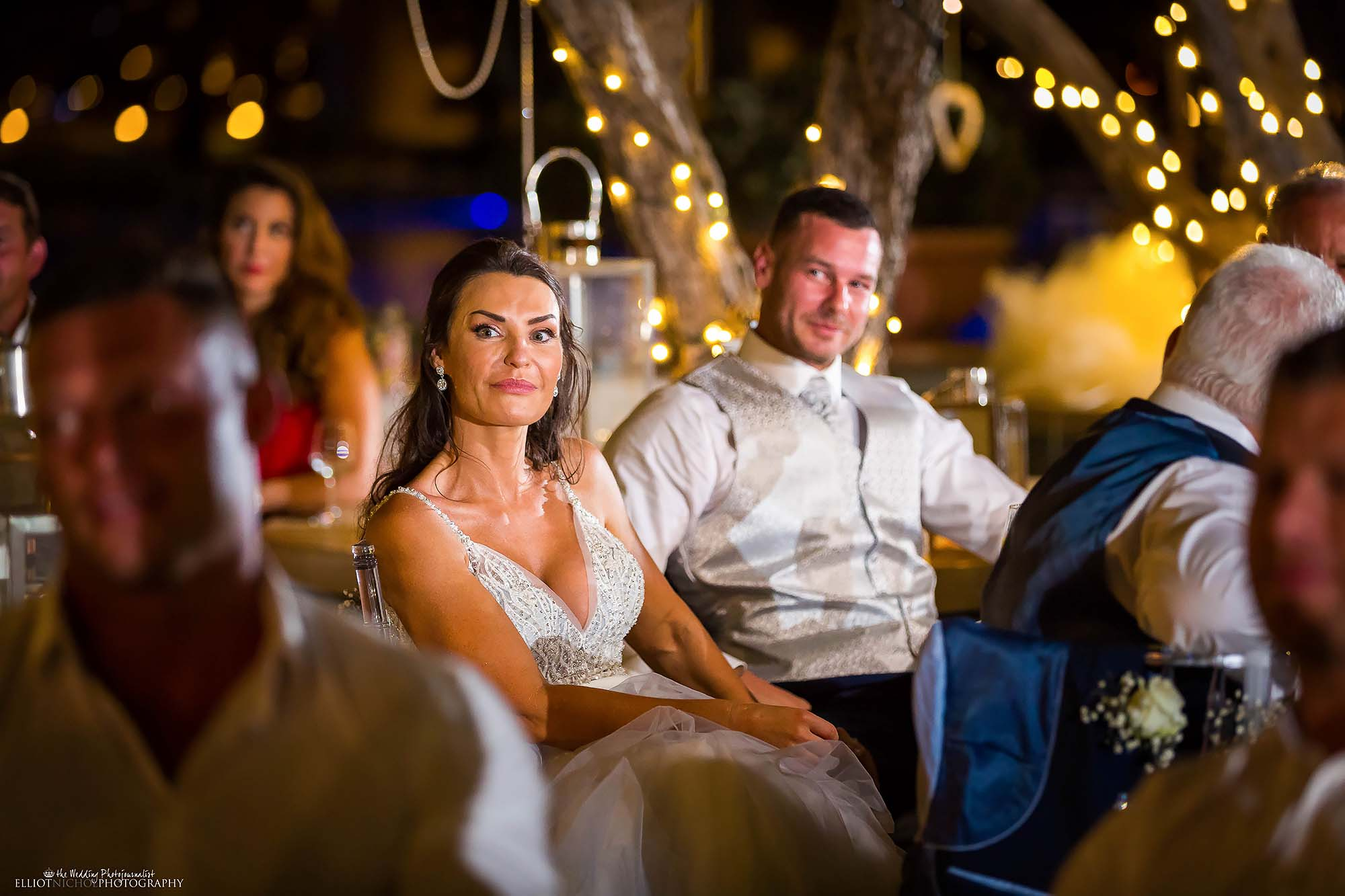 Candid photo of the bride and groom while they listen to their wedding speeches.