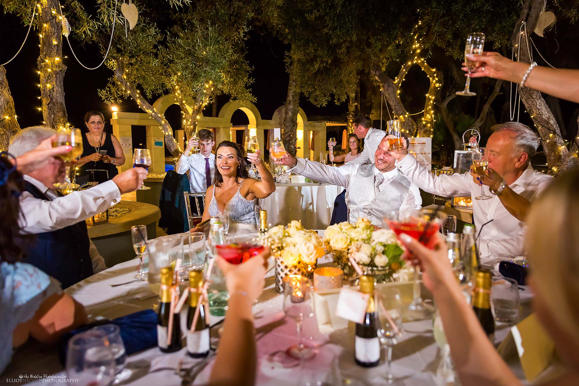 Top table raises their glasses in a toast to the bride and groom. Wedding Photography by Elliot Nichol.