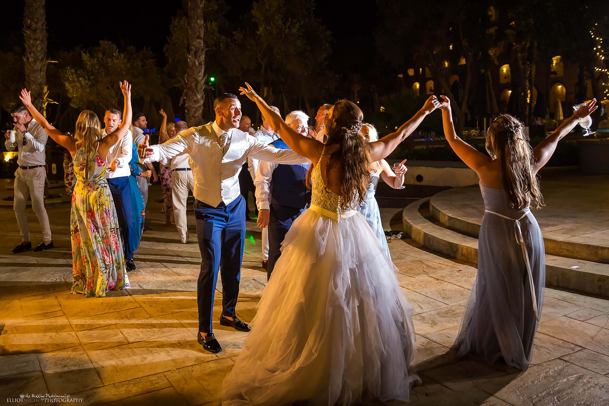 Bride and groom partying on the dance floor with their wedding guests.