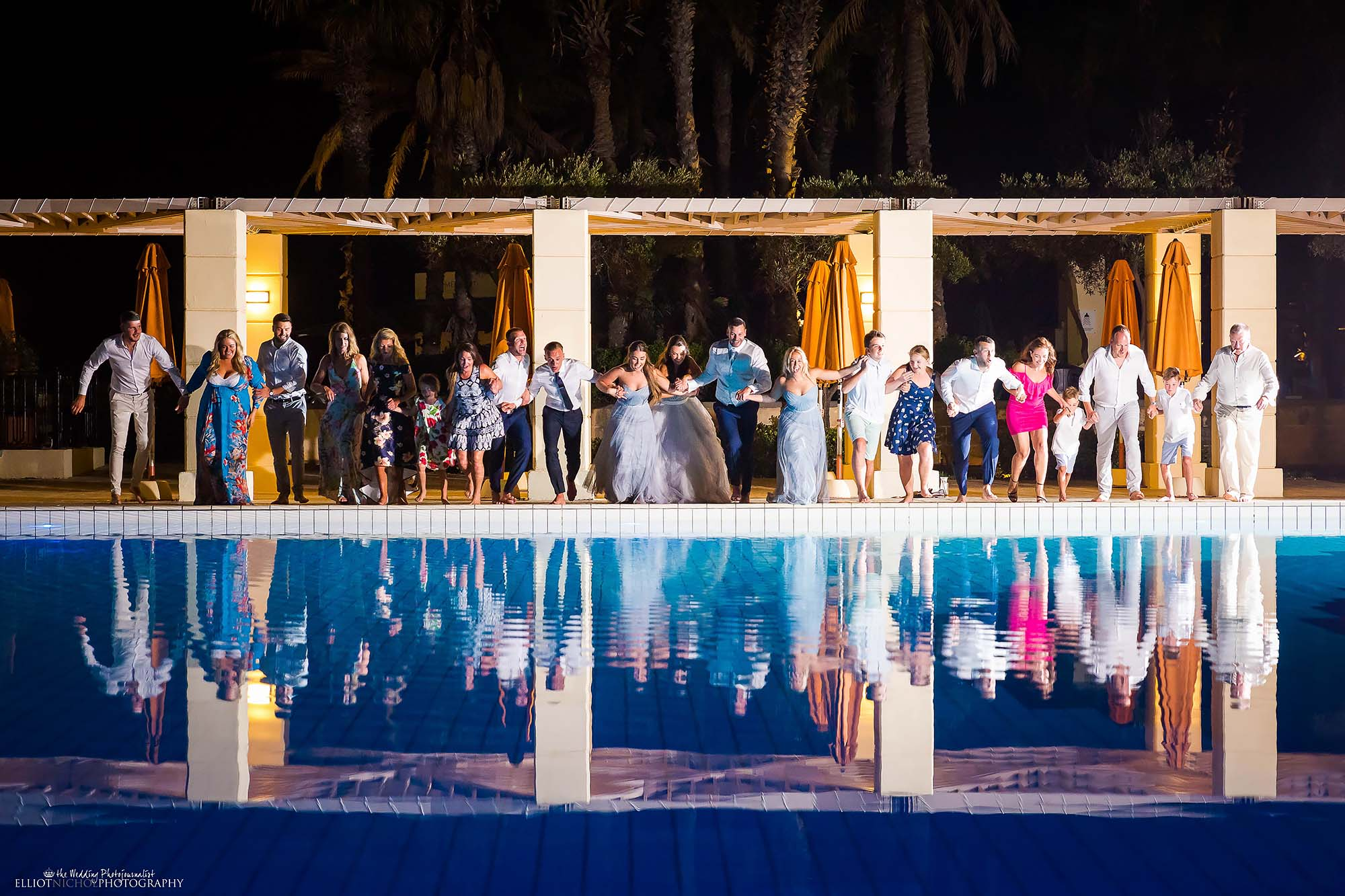 Blue wedding dress bride jumping into a swimming pool with her wedding guests.
