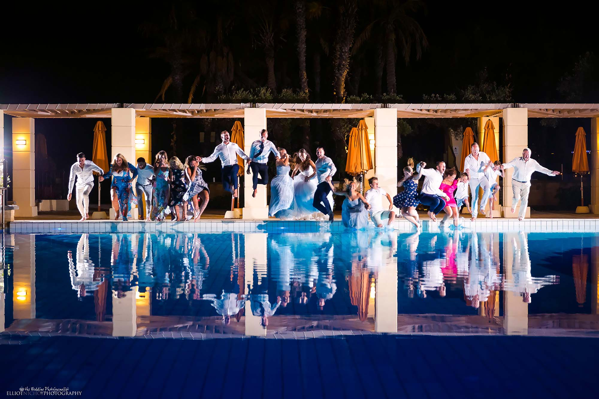 destination wedding party all jump into a swimming pool fully clothed.
