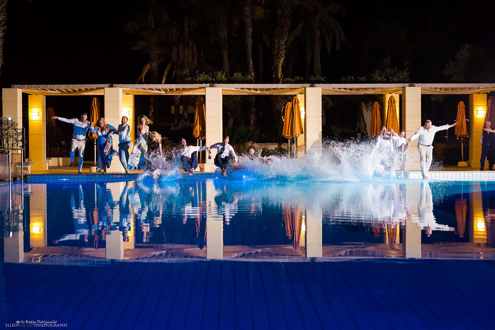 Bride and groom jump into a hotel swimming pool with their wedding guests. Wedding photography by Elliot Nichol.