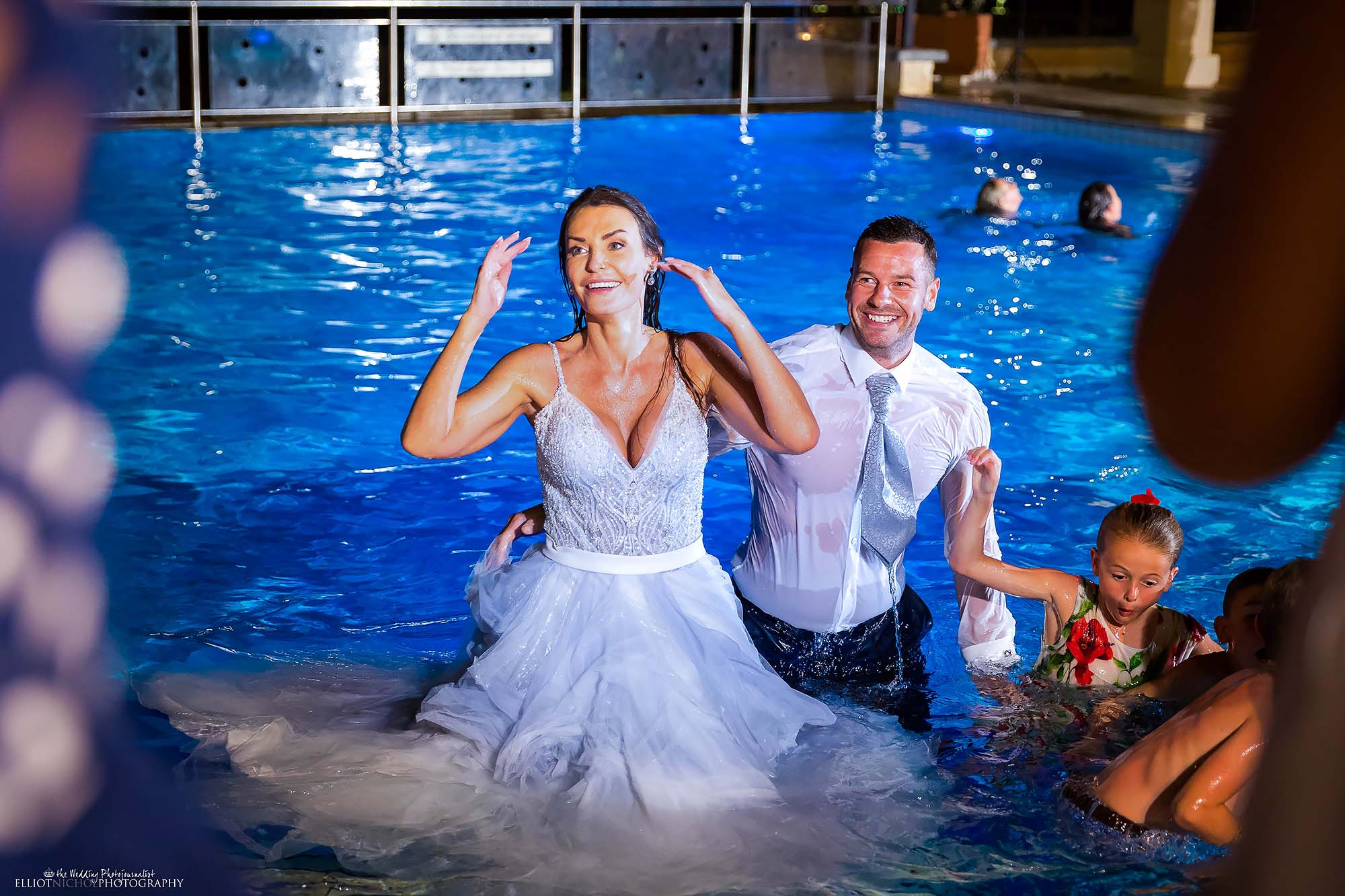 Bride and groom in the swimming pool after jumping in with their wedding guests.