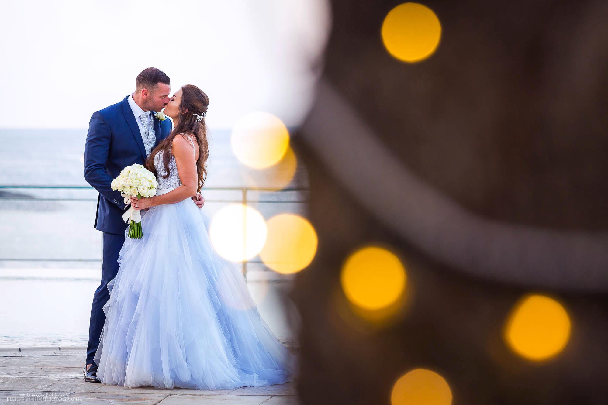 Bride in her blue wedding dress kissing her groom. Wedding photography by Newcastle based photographer Elliot Nichol.