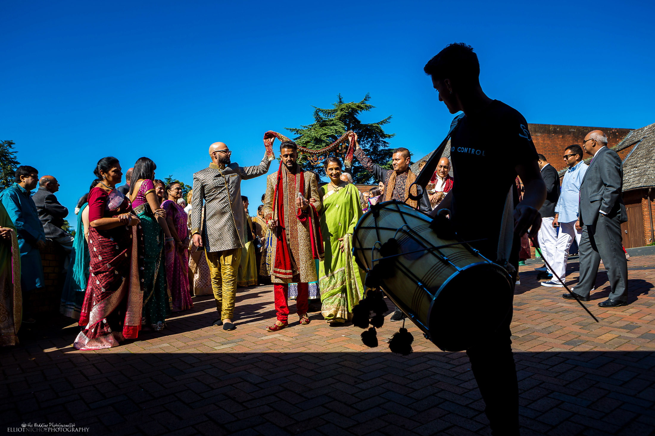 Indian groom walks towards the Hindu wedding ceremony location, surrounded by family members. Photo by Elliot Nichol Photography based in the Northeast of England.